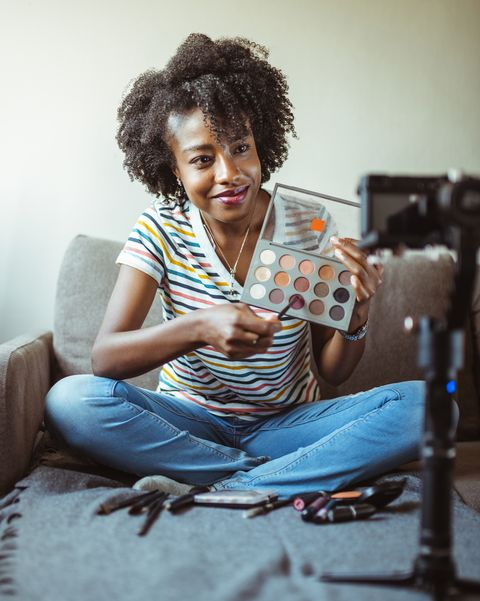 beautiful african american woman beauty vlogger recording makeup tutorial