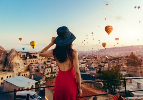 beautiful asian woman watching  colorful hot air balloons flying over the valley at cappadocia, turkey turkey cappadocia fairytale scenery of mountains