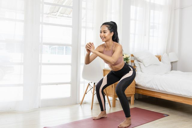 a beautiful asian woman's fitness at home instead of going to the gym she is doing squats on a yoga mat in the bedroom she wears sportswear exercise concept for good shape