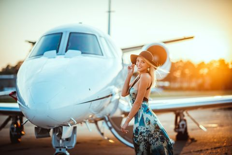 beautiful blond woman standing next to a nose cone of a private jet at sunset