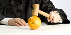 Beautiful blonde judge in black robe with gavel and orange.