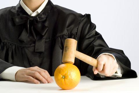Beautiful blonde judge in black robe with gavel and orange.