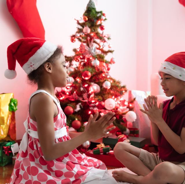 beautiful brother and sister playing games sitting next to christmas tree on the floor