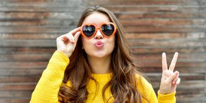 Beautiful brunette woman in sunglasses blowing lips kiss. wooden background.