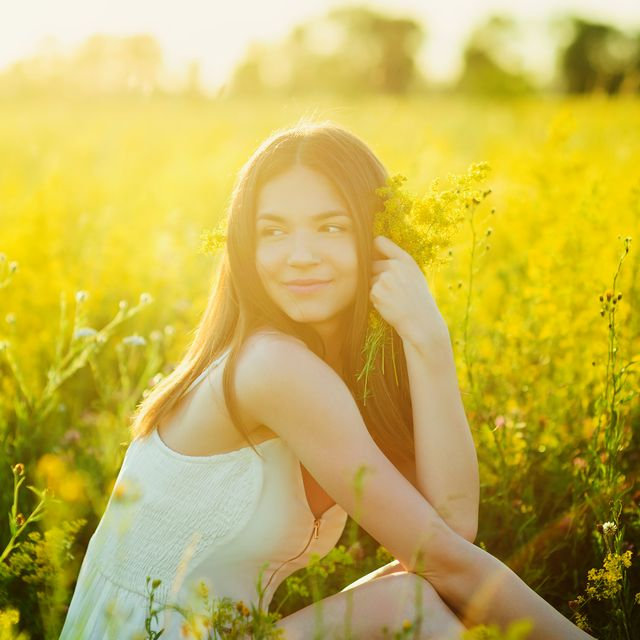 beautiful caucasian girl in the flowers field in summer sunset healthy lifestyle