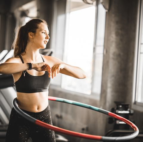 beautiful caucasian young woman doing hula hoop in step waist hooping forward stance young woman doing hula hoop during an exercise class in a gym  healthy sports lifestyle fitness healthy concept