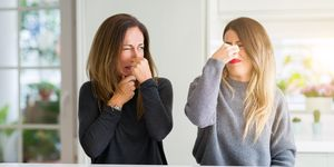 Beautiful family of mother and daughter together at home smelling something stinky and disgusting, intolerable smell, holding breath with fingers on nose. Bad smells concept.