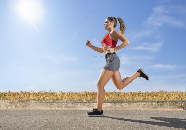 beautiful female athlete running fast in nature