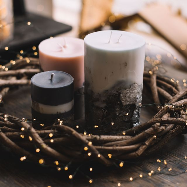 beautiful festive hand made candles with concrete in it and a wooden florist wreath around it with firefly garland on a rustic old wooden table with festive decoration on the background