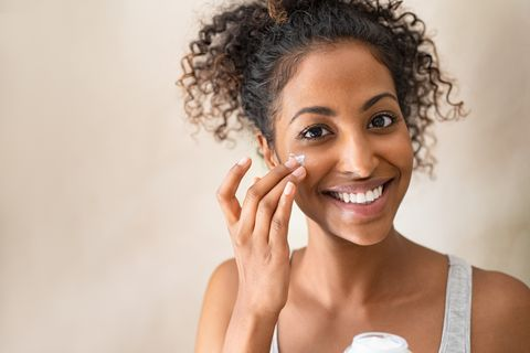 beautiful girl applying face cream