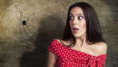 Vrouw staat naast spinnenweb en is bang