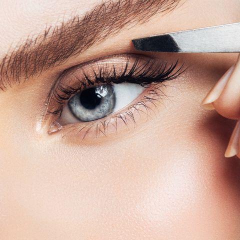Beautiful girl plucks eyebrows