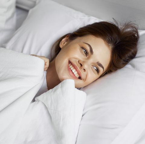 Beautiful girl woke up in her bed in the morning and smiling