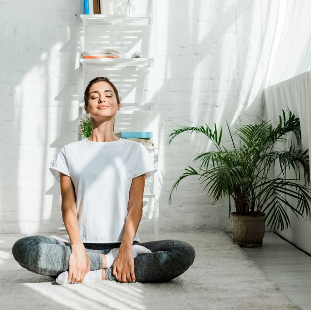 beautiful happy girl with closed eyes practicing yoga in lotus position in bedroom in the morning
