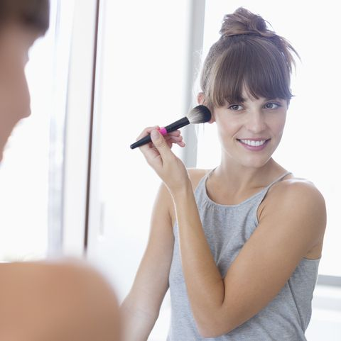 Beautiful happy woman applying make-up on her face