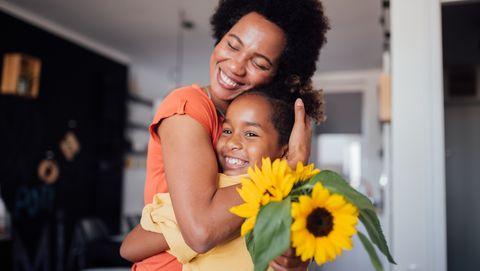 meisje geeft zonnebloem aan moeder