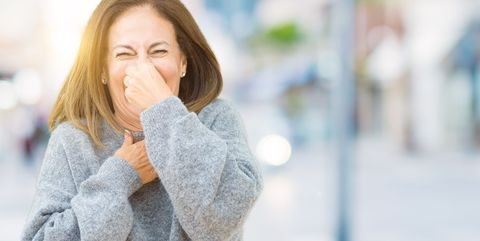 Beautiful middle age woman wearing winter sweater over isolated background smelling something stinky and disgusting, intolerable smell, holding breath with fingers on nose. Bad smells concept.