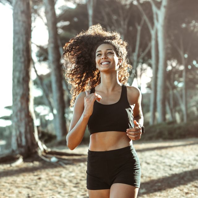 beautiful smiley woman doing sport in a pine forest by the sea