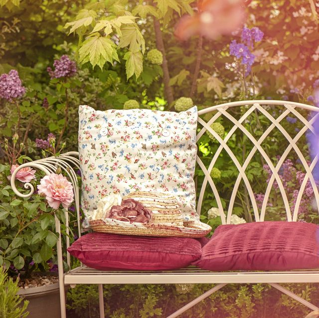 A beautiful summer cast iron garden chair with cushions and a summer hat, shabby chic scene