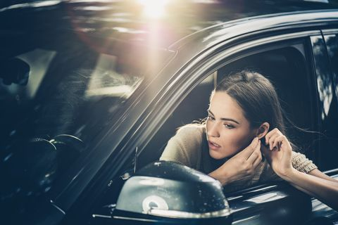 beautiful woman adjusting her earring in a car