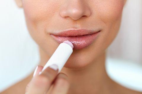 Beautiful Woman Applying Lip Protector On Lips Skin. Beauty