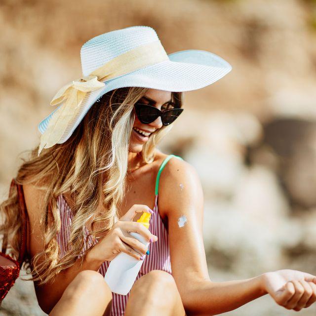 beautiful woman at beach using sun lotion
