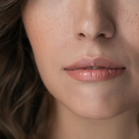 beautiful woman bite lips and freckles close up face