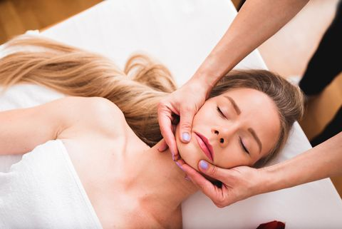 beautiful woman doing facial massage in a spa salon