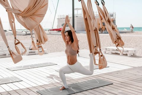 a beautiful woman engaged in antigravity yoga outdoors by the sea on the beach