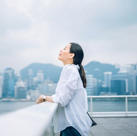 beautiful woman enjoying the fresh air with eyes closed against city background
