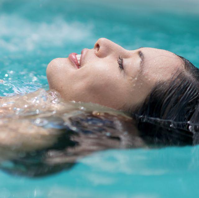 beautiful woman floating in the swimming pool