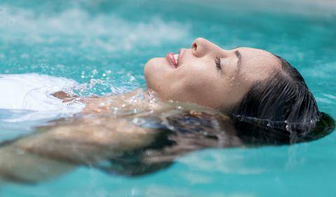 Mujer en al piscina con los ojos cerrados.