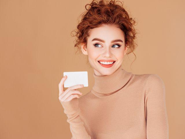 una ragazza regge un biglietto di auguri