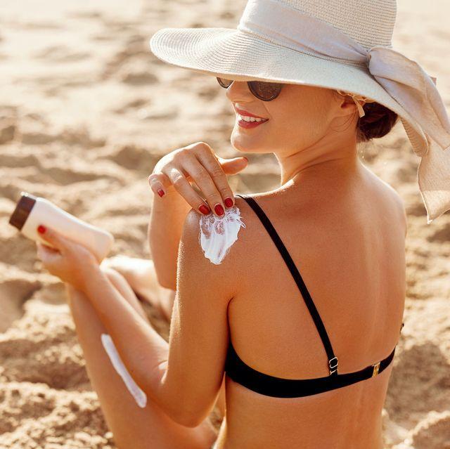 beautiful woman in bikini applying sunscreen