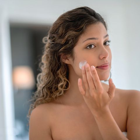 Beautiful woman in the bathroom applying cream on her face