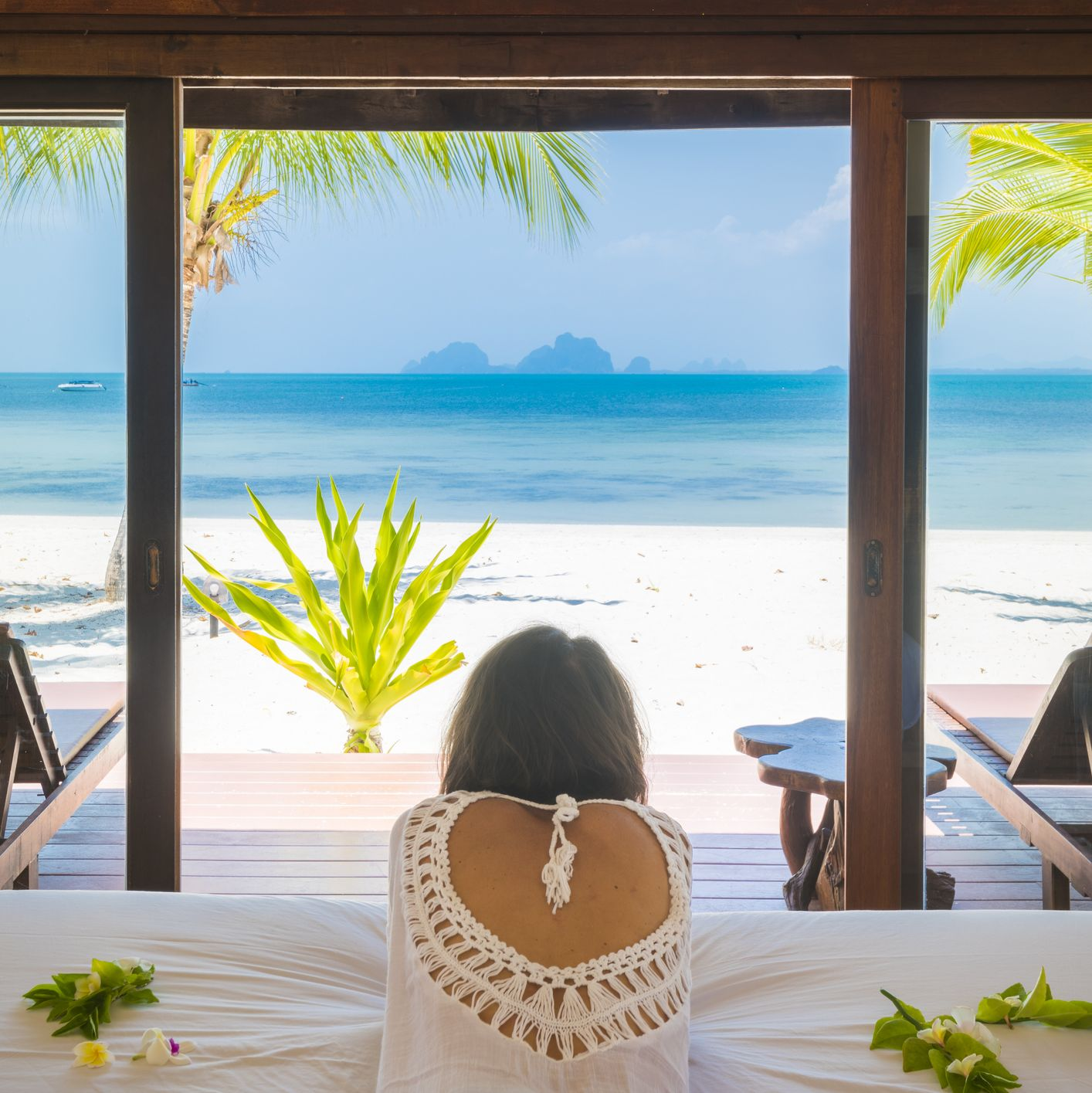 Beautiful woman looking away at the beach from a beachfront bungalow, Thailand.