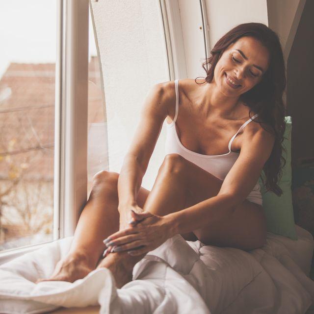 beautiful woman massaging legs by the window
