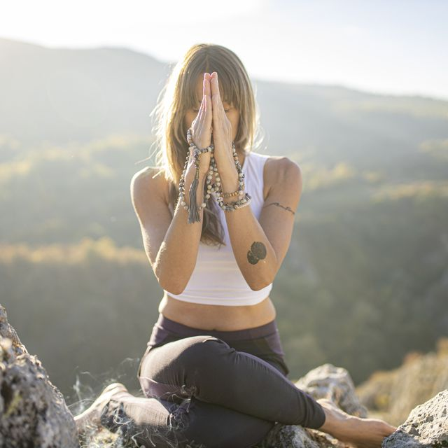 mujer con tatuajes haciendo yoga