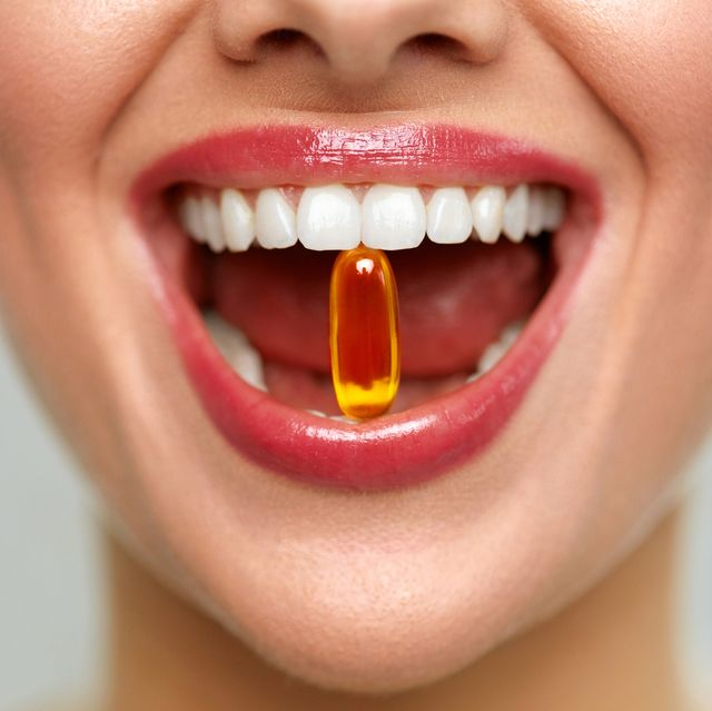 beautiful woman mouth with pill in teeth