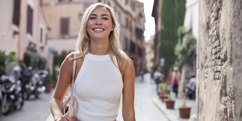 Beautiful woman walking on cobblestone street