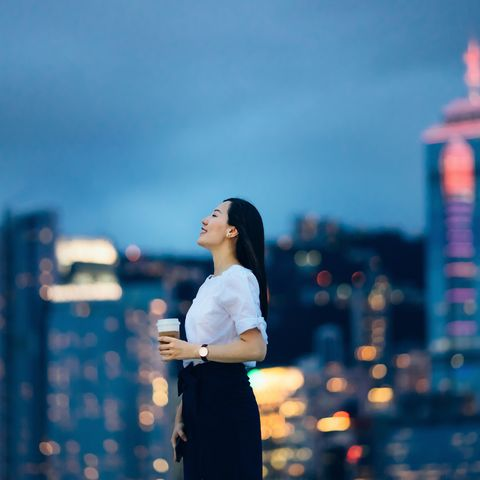 beautiful young asian woman eyes closed and relaxing against the spectacular urban city skyline by the promenade of victoria harbour at dusk
