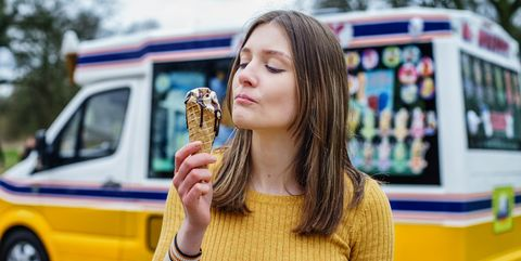Beautiful Young English Lady eat Ice Cream in front of ice cream van in uk