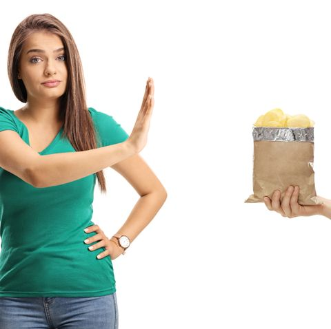 beautiful young female gesturing refusal with her hand to a packet of crisps