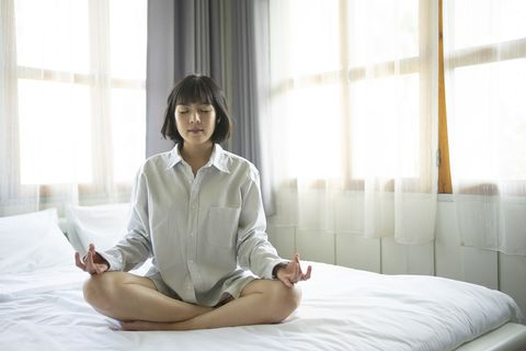 beautiful young female pose and practice meditation on the bed