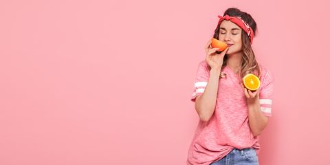 Beautiful young girl in pink t-shirt, keeps funny sexy orange on pink background. Summer and rest