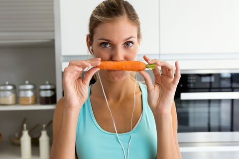 Beautiful young sporty woman playing with carrot while listening to music with earphones in the kitchen.