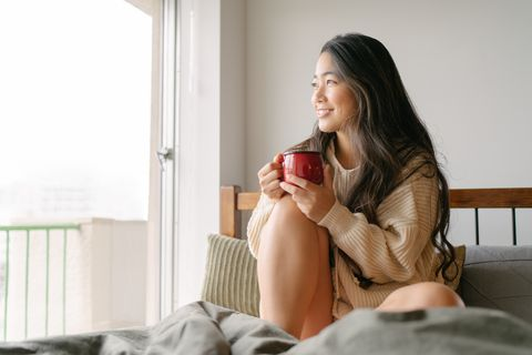 beautiful young woman drinking hot drink in her bed in the morning