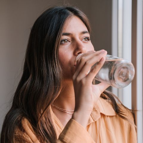 Beautiful Young Woman Drinking Water In Glass Bottle By Window