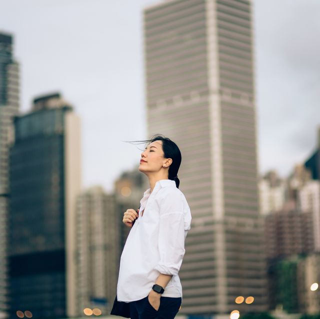 beautiful young woman with eyes closed enjoying the tranquility and gentle wind breeze against urban city skyline