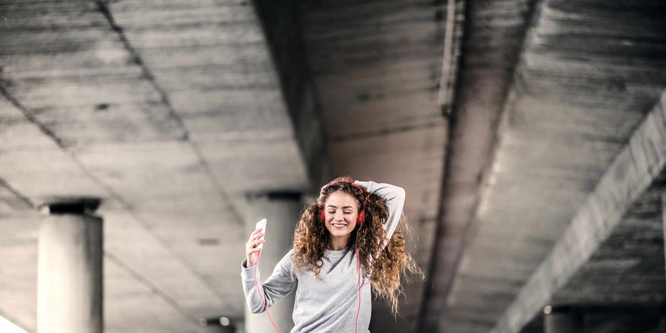A beautiful young woman with smartphone and red headphones under the bridge in the city, listening to music.